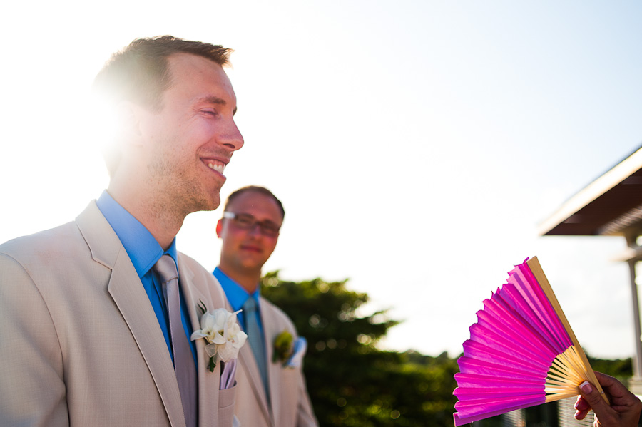 Hot groom being fanned by a guest during wedding ceremony