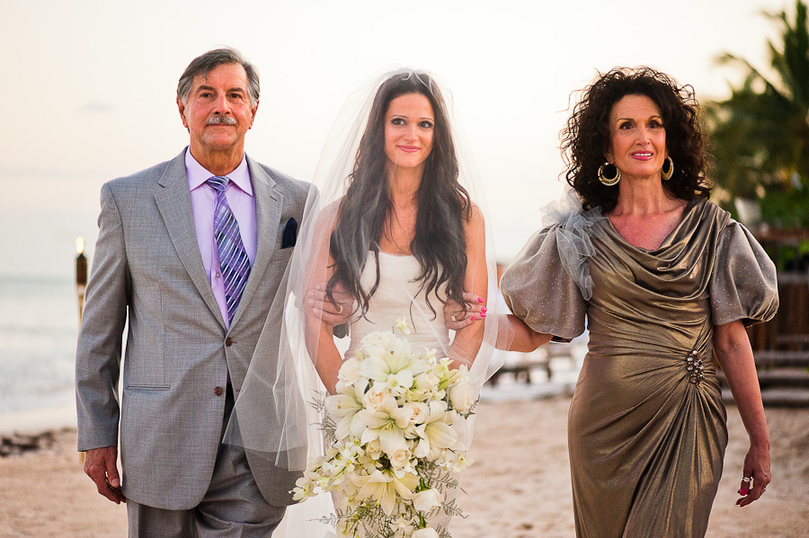 Bride walking down the aisle with her parents, beach ceremony