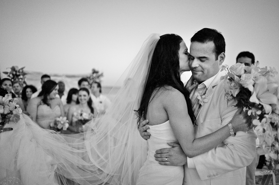 Bride kisses groom on the cheek during beach ceremony at the Rosewood Wedding