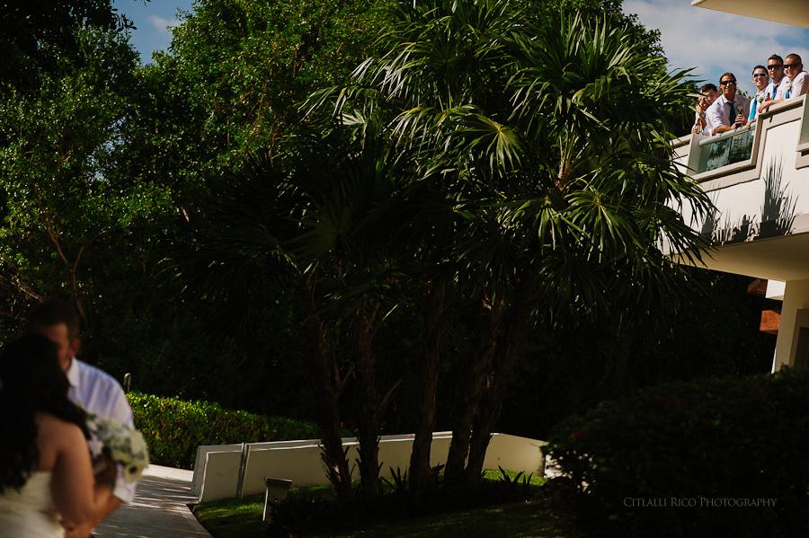 Bride and groom kissing groomsmen watching funny Cancun mexico beach wedding SJ Bay Blue Grand