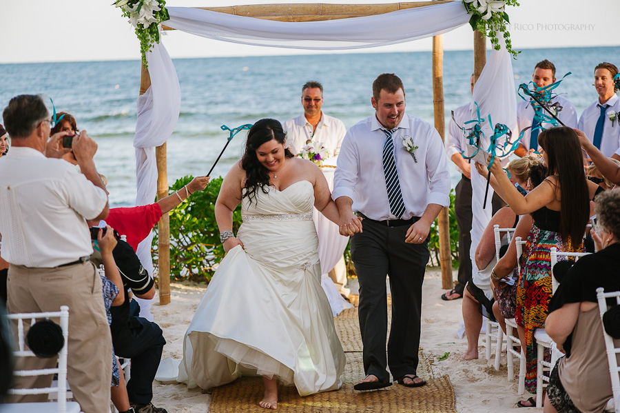 Bride and groom walking out the isle fun Cancun mexico beach wedding SJ Bay Blue Grand