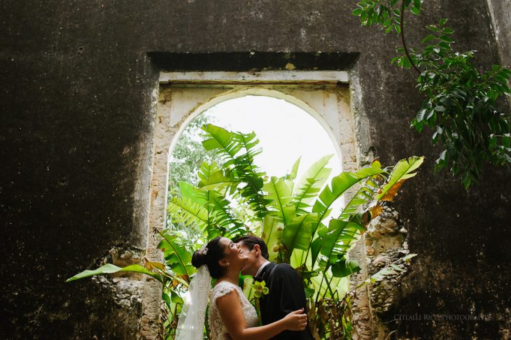 Hacienda portrait of bride and groom with green leafs