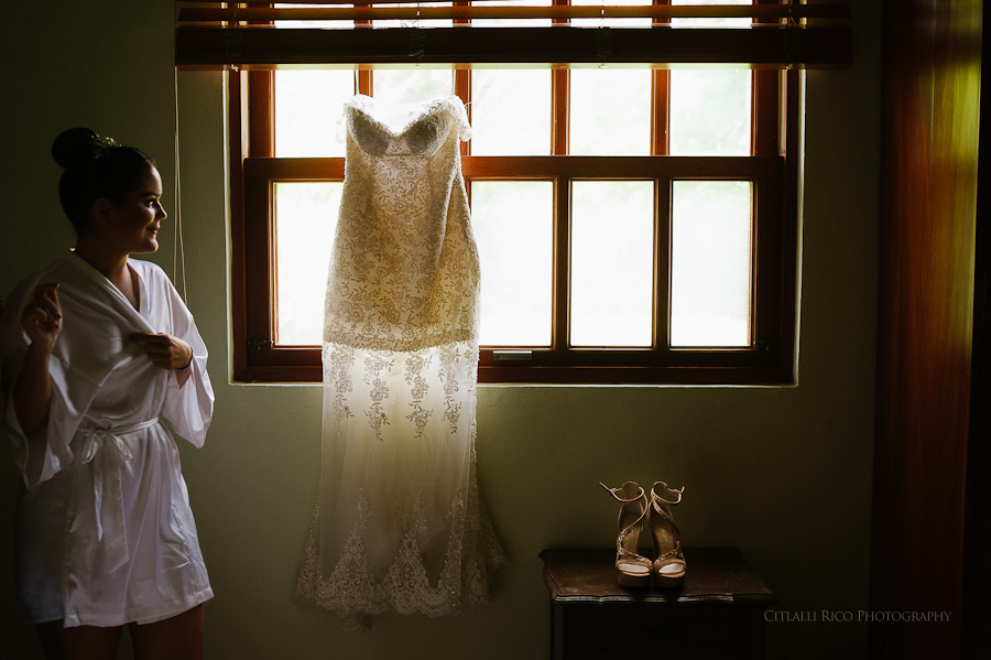 Bride looking at her dress hanging from the window