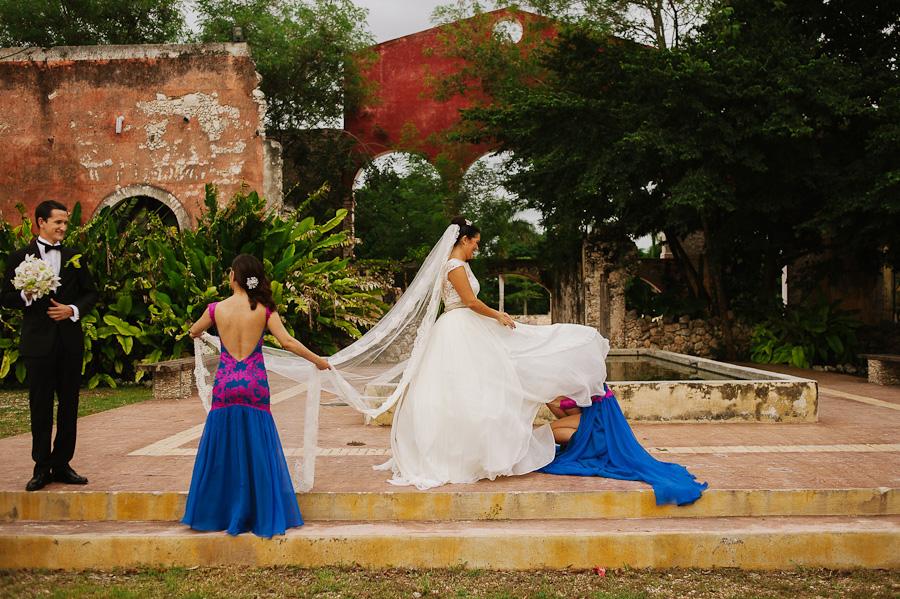 Bridesmaids helping bride with dress in Hacienda wedding