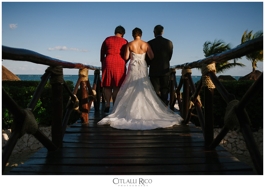 Bride walking down the aisle with her parents for Azul Beach Ceremony