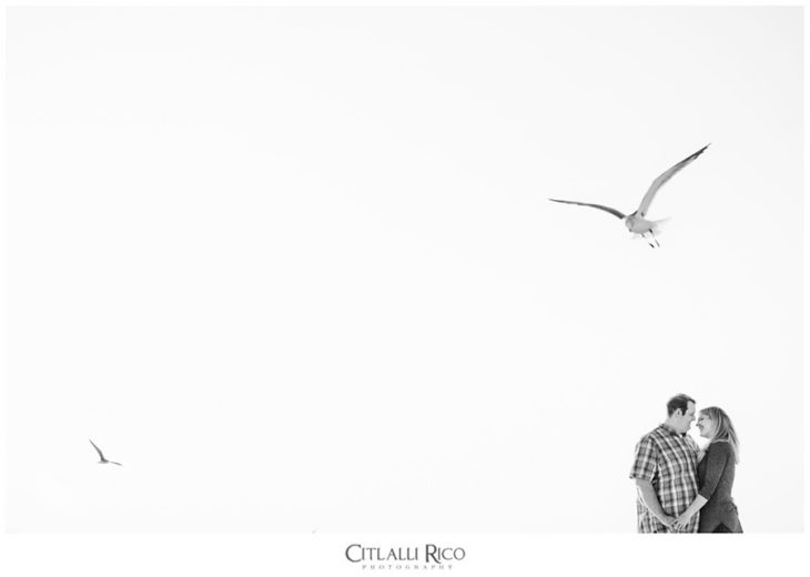 Anniversary black and white photos on the beach with seagulls and white sky