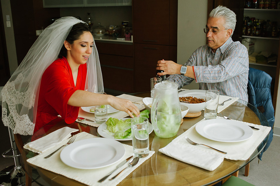 Father of the bride and bride having lunch before ceremony