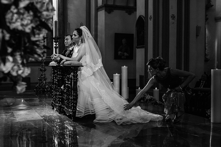 Bride and groom at the altar while bridesmaid fixes the dress