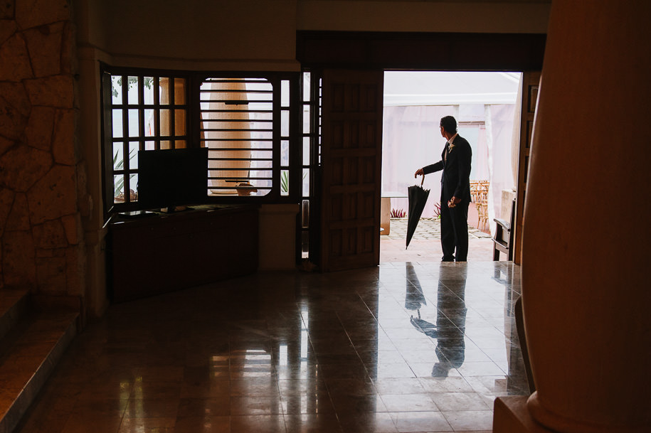 groom arriving to brides house on rainy day