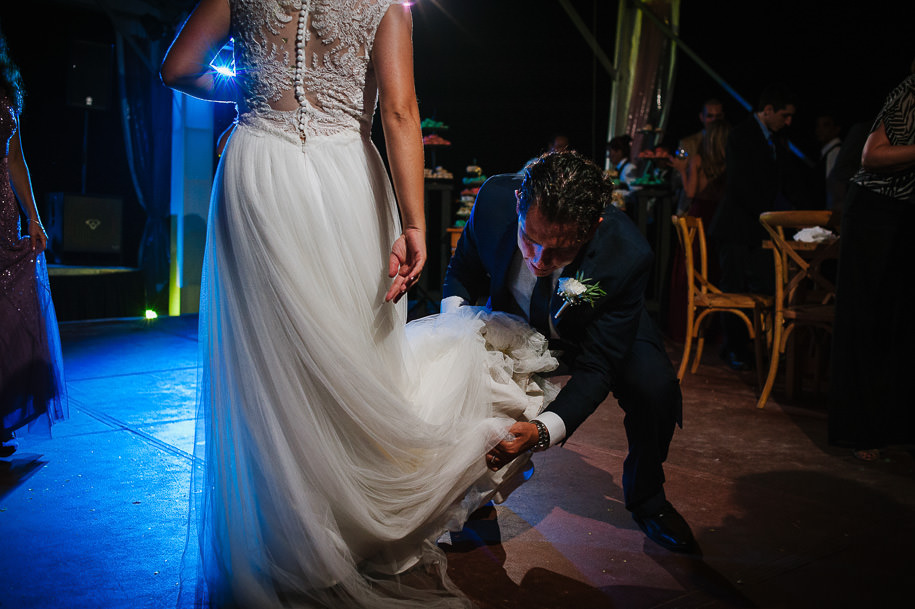 Groom helping bride with the dress during reception