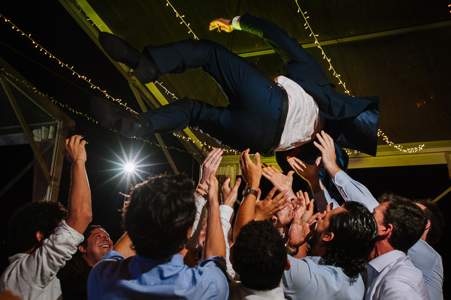 Groom being tossed by his friends during wedding reception