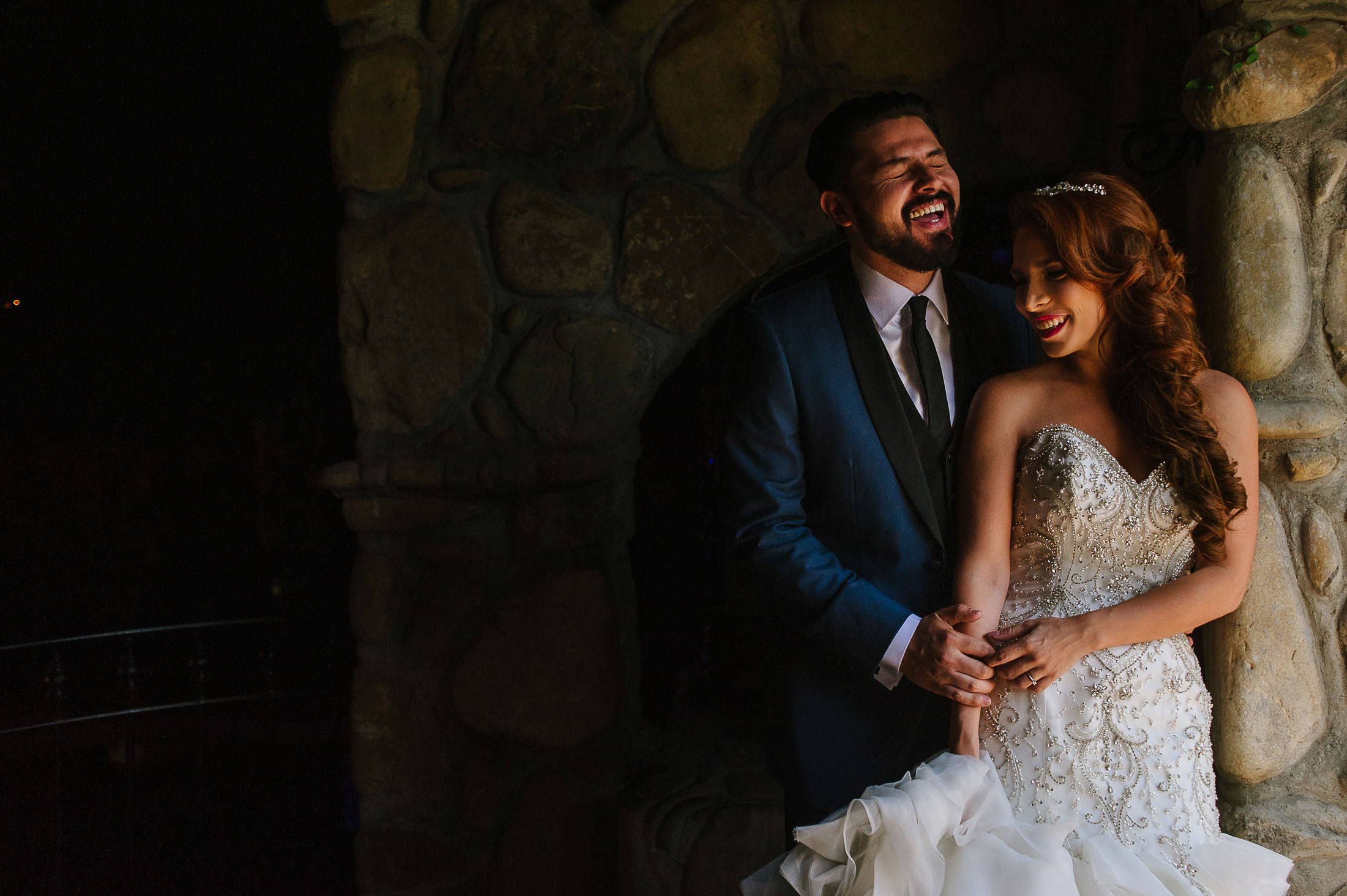 Groom and bride laughing by a stone wall in Santiago portraits