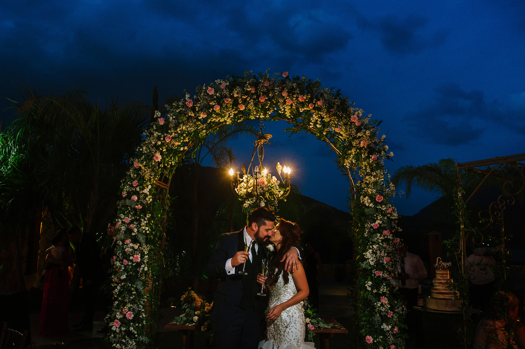 Bride & groom under beautiful flower arch decoration reception Mexican wedding