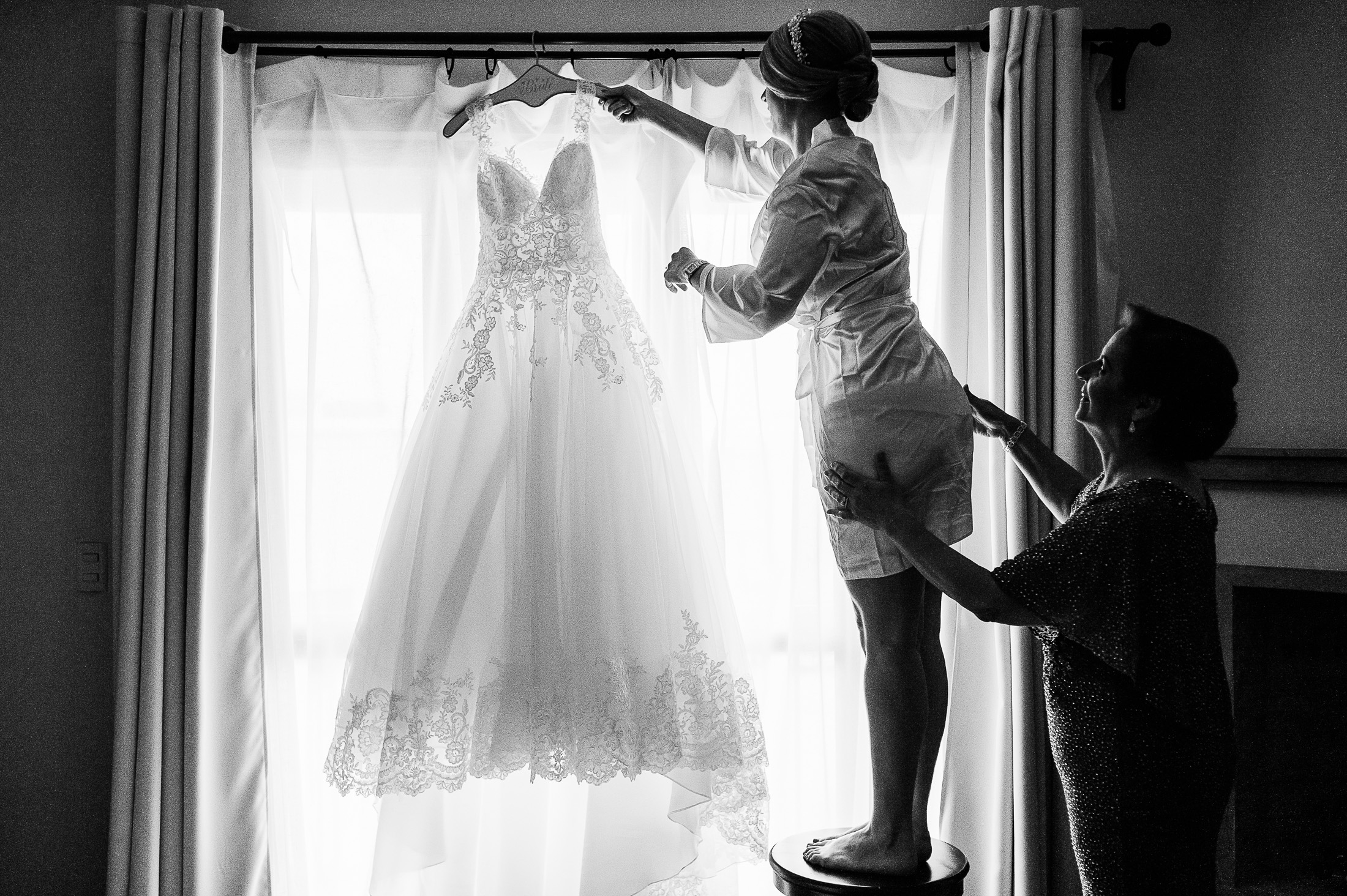 Bride hanging dress from the window Mom helping