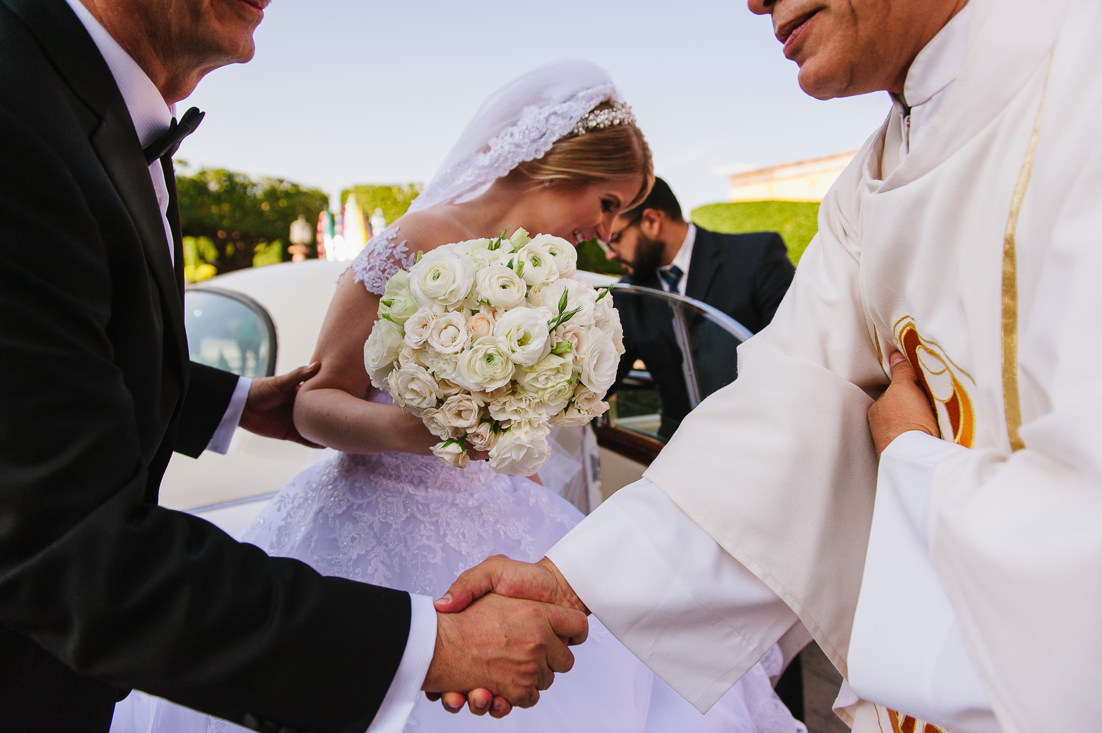 Priest shakes hand of Father of the bride before the ceremony