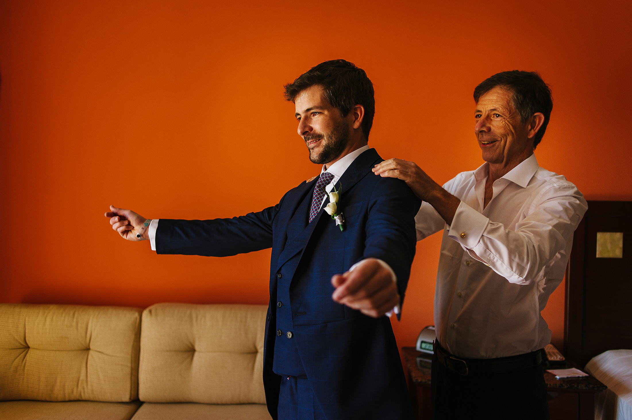 Groom being helped by his Dad to put his jacket on