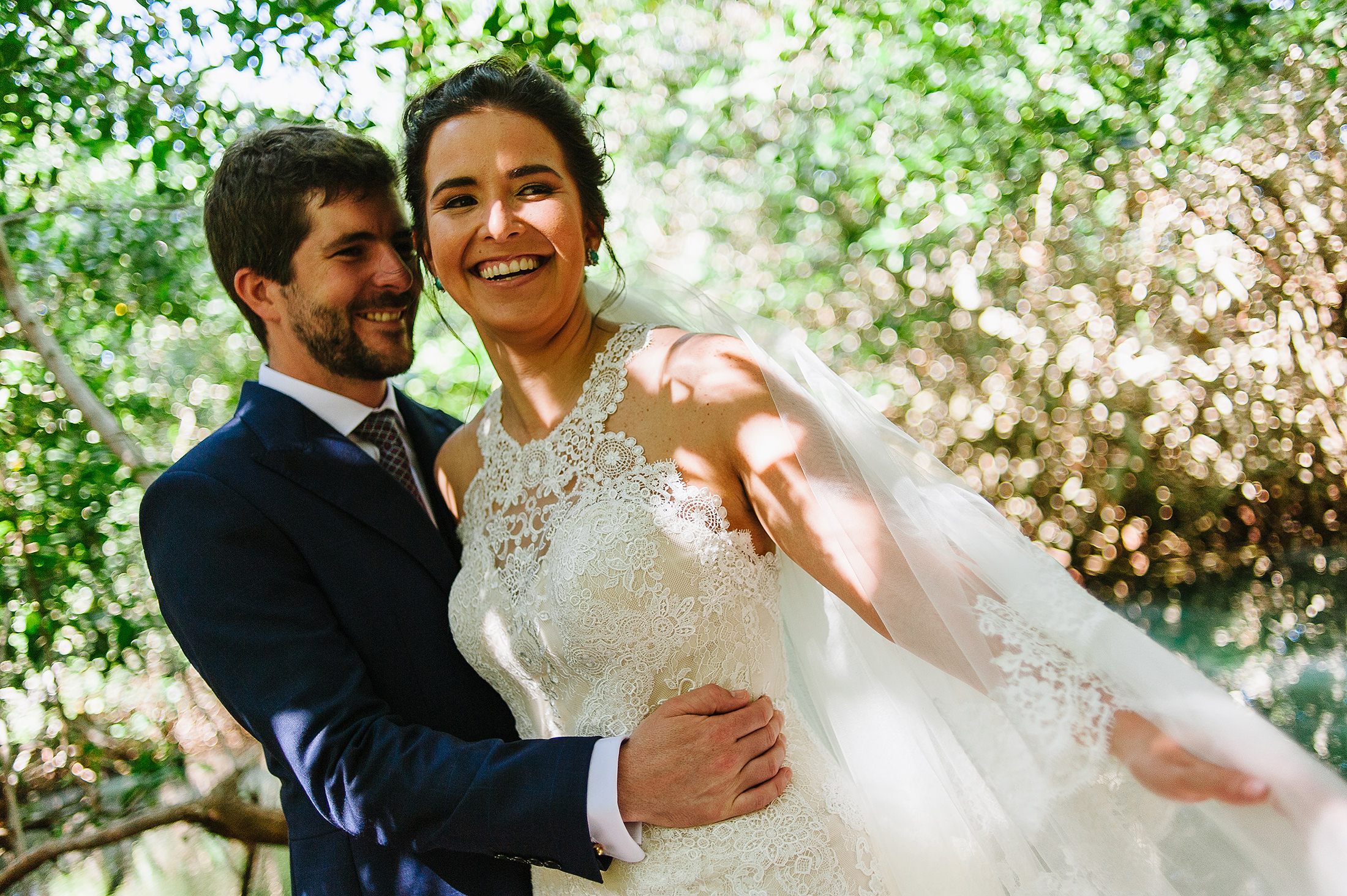 Bride and groom smiling during portraits playing with veil and beautiful bokeh