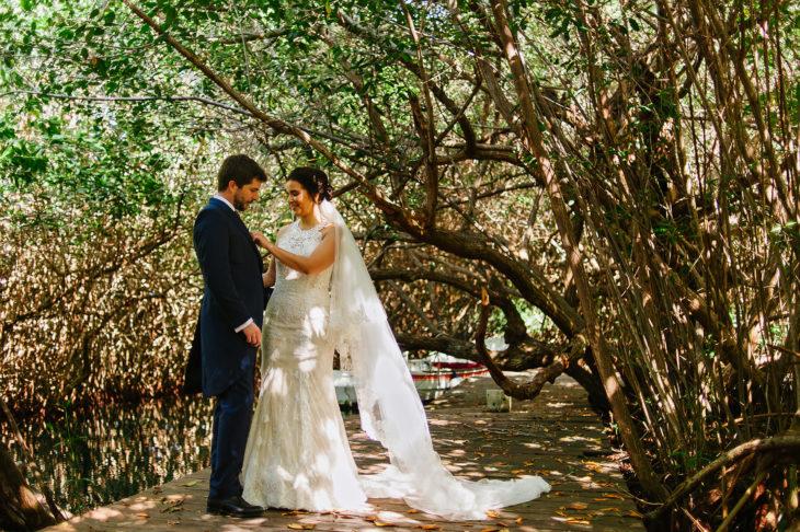 Bride fixing groom's buttoniere near the cenote