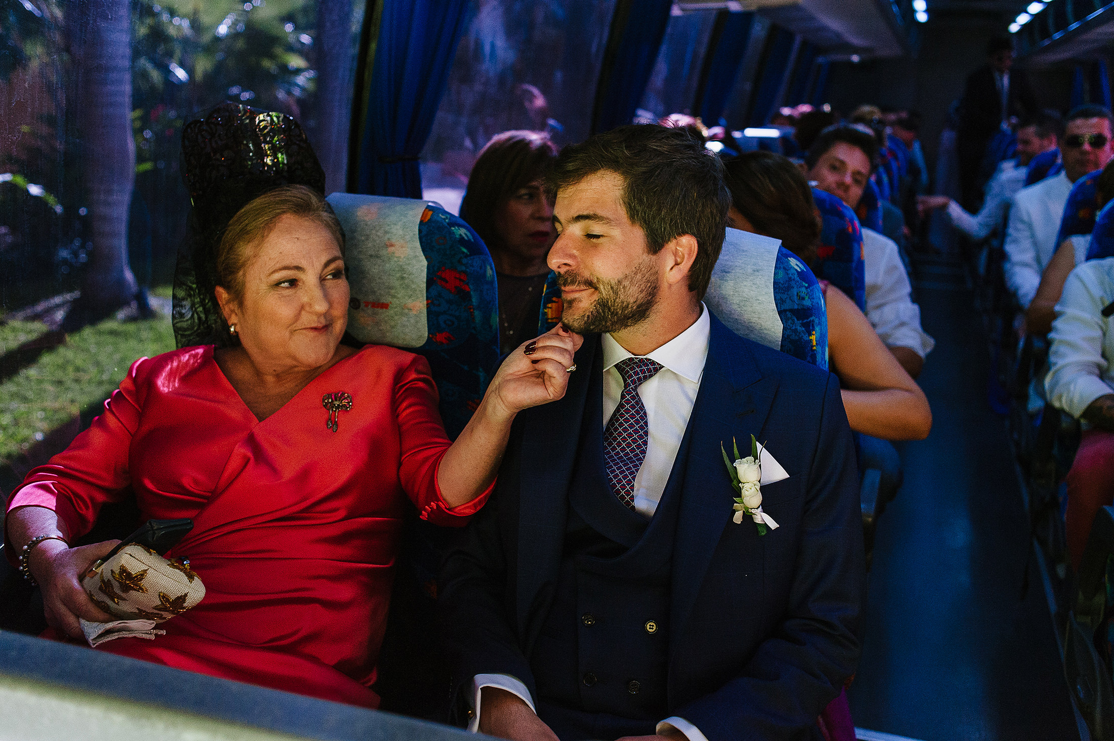 Mom touching groom's face on the bus heading to ceremony