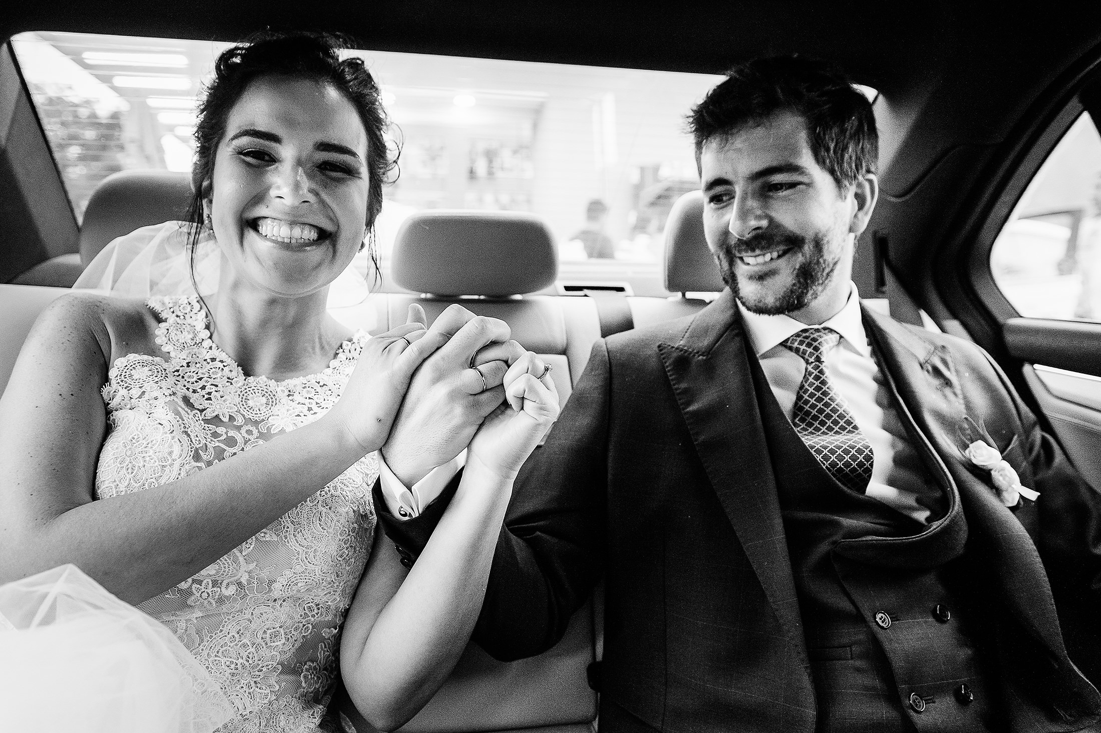 Bride and groom in the car holding hands showing rings