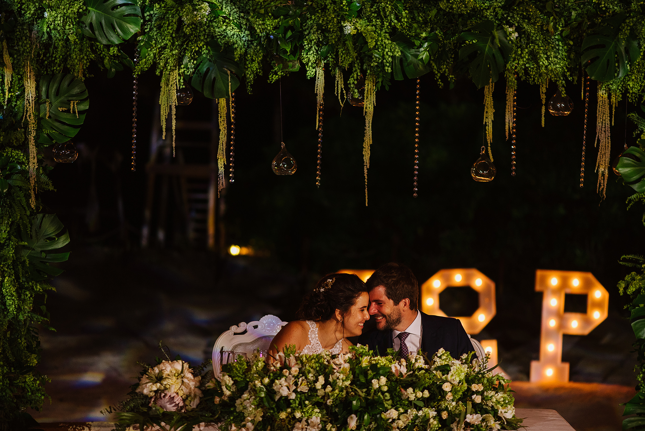 Bride and groom smiling sitting at the head table with beautiful wedding decoration