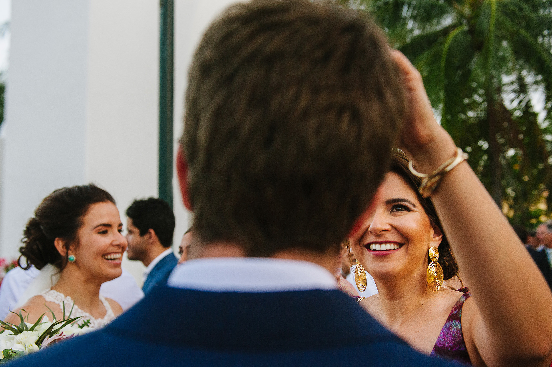 Bridesmaid fixing groom's hair after ceremony