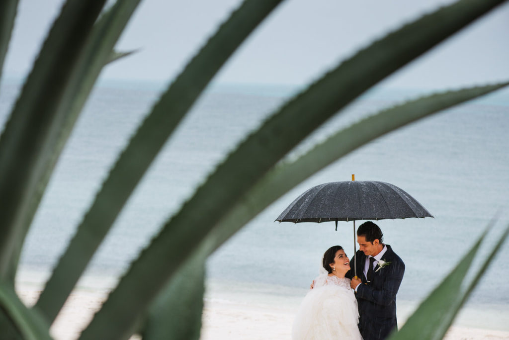Couple creative portrait in the rain for beach outdoor wedding