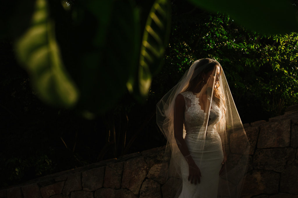 Bride with gorgeous daylight under the veil surrounded by green leaves in Xcaret Park