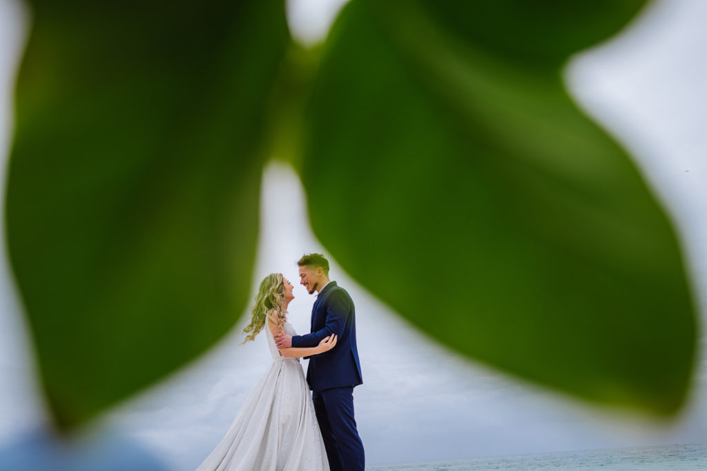 Bride and groom standing under green leaves against blue sky