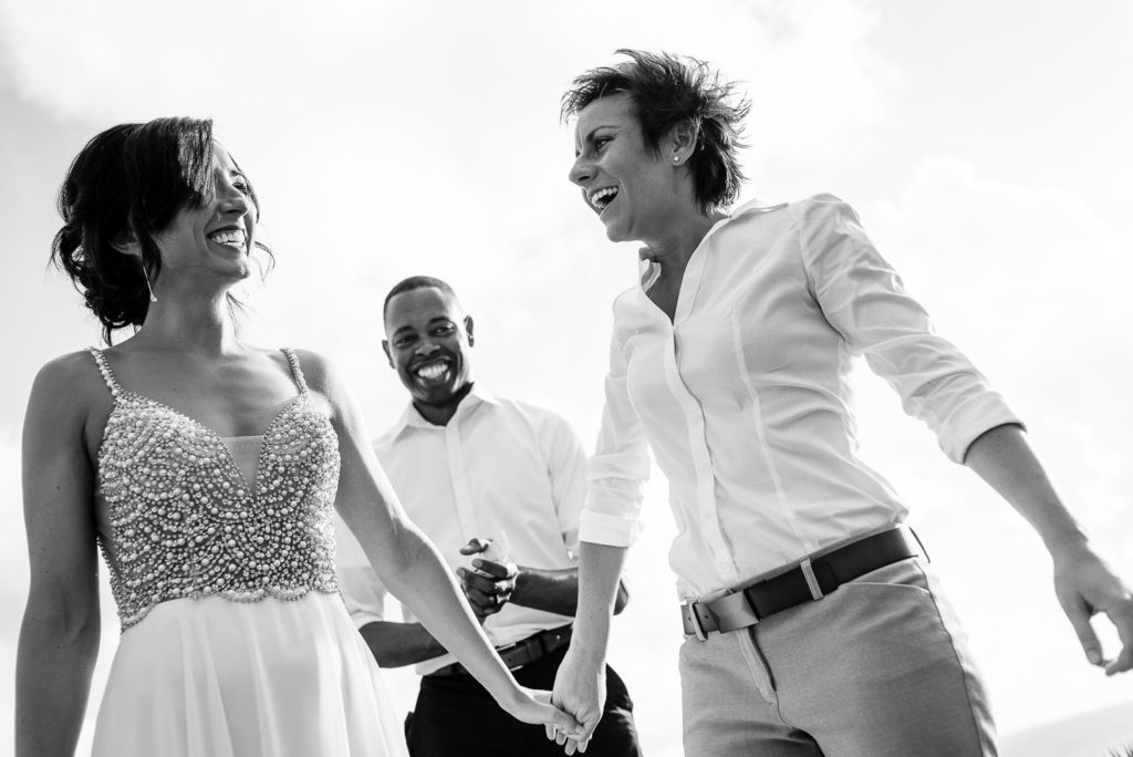 Black and white image same sex wedding ceremony brides smiling with officiant in the back