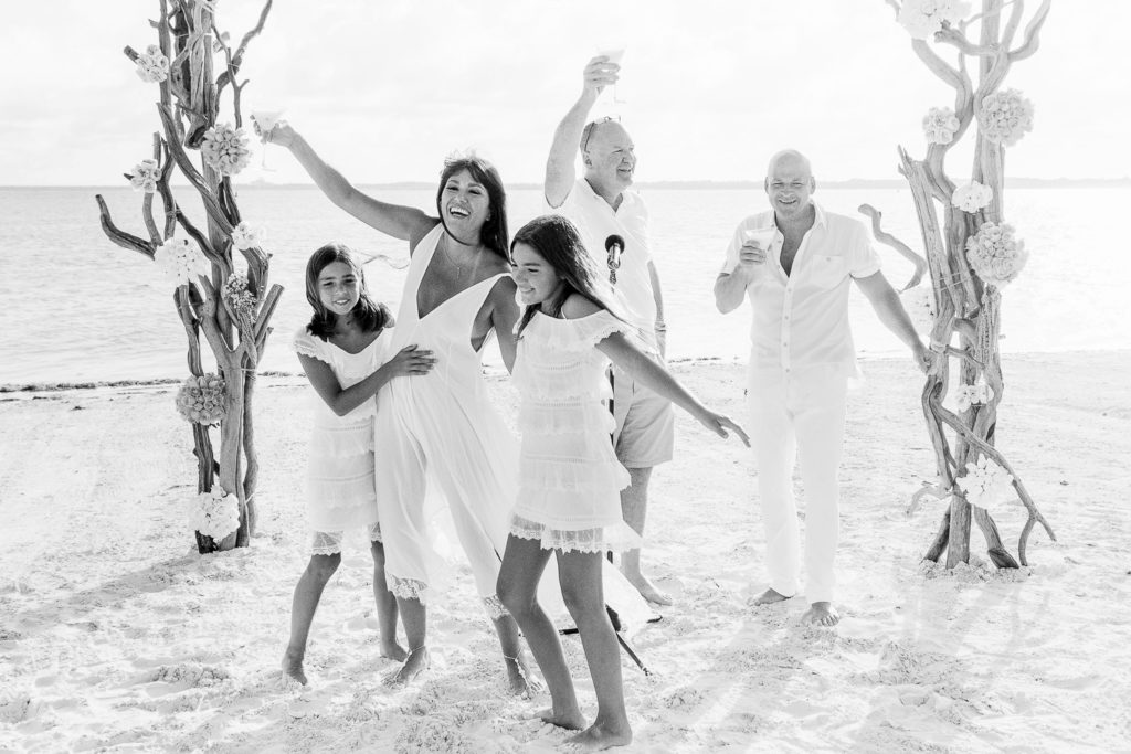 Nizuc wedding ceremony on the beach with bride and guests celebrating with drinks and two daughters