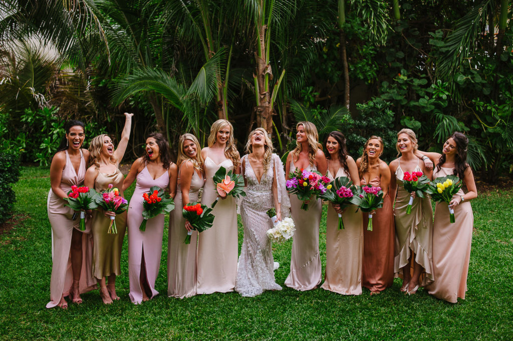 Bride and bridesmaids posing and laughing together in the Viceroy Riviera Maya garden