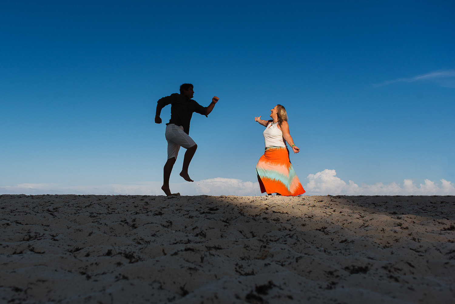 couple jumping on the beach with groom as a silohuette and bride with the sun against blue sky