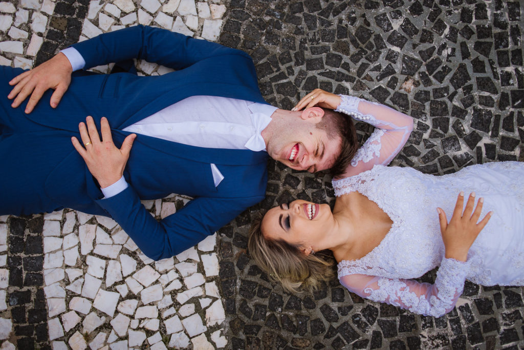 Brasilian couple laying on the ground laughing, groom with tailored blue suit. Black and white tile floor.