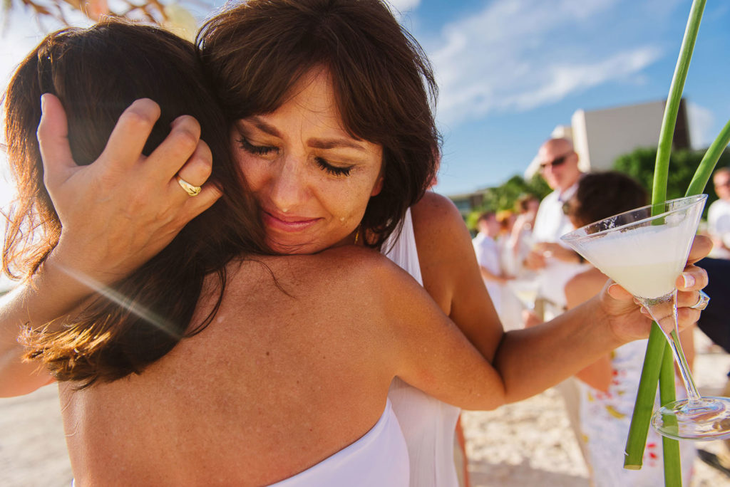 Bride with happy tears hugging her best friend while holding a pisco sour on Nizuc beach after ceremony