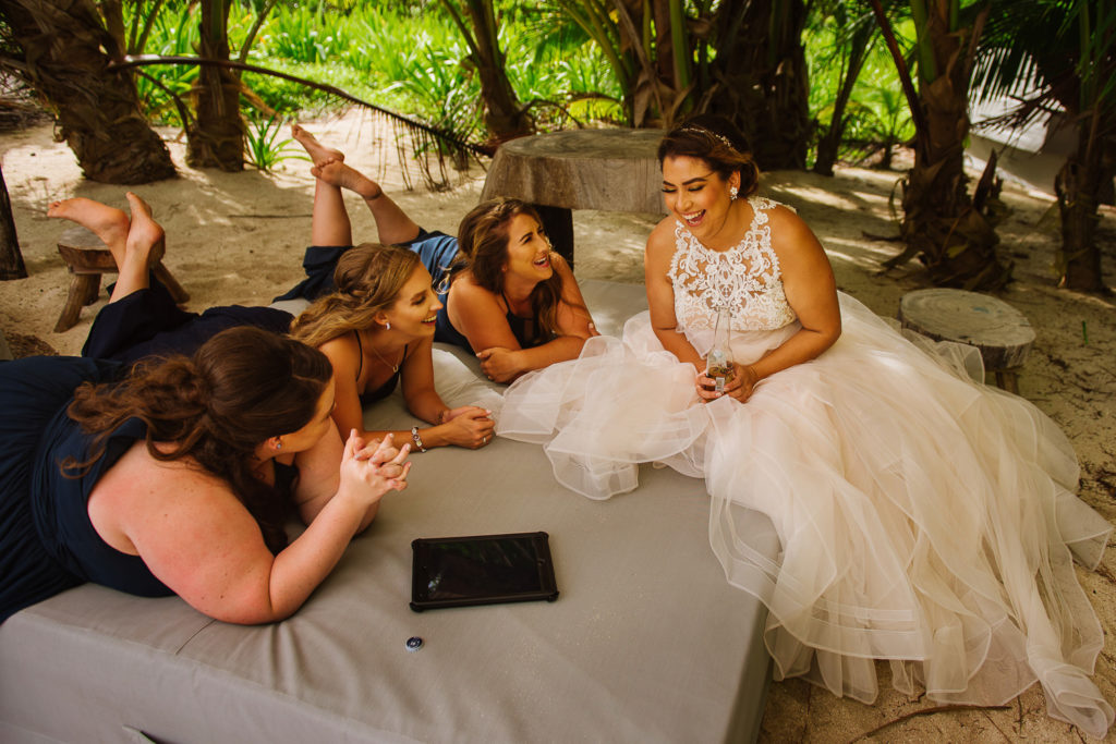 Bride and bridesmaids at Blue Venado sitting on a beach mattress laughing