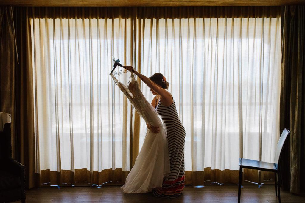 Bride at Hard Rock Riviera Maya room holding her wedding dress