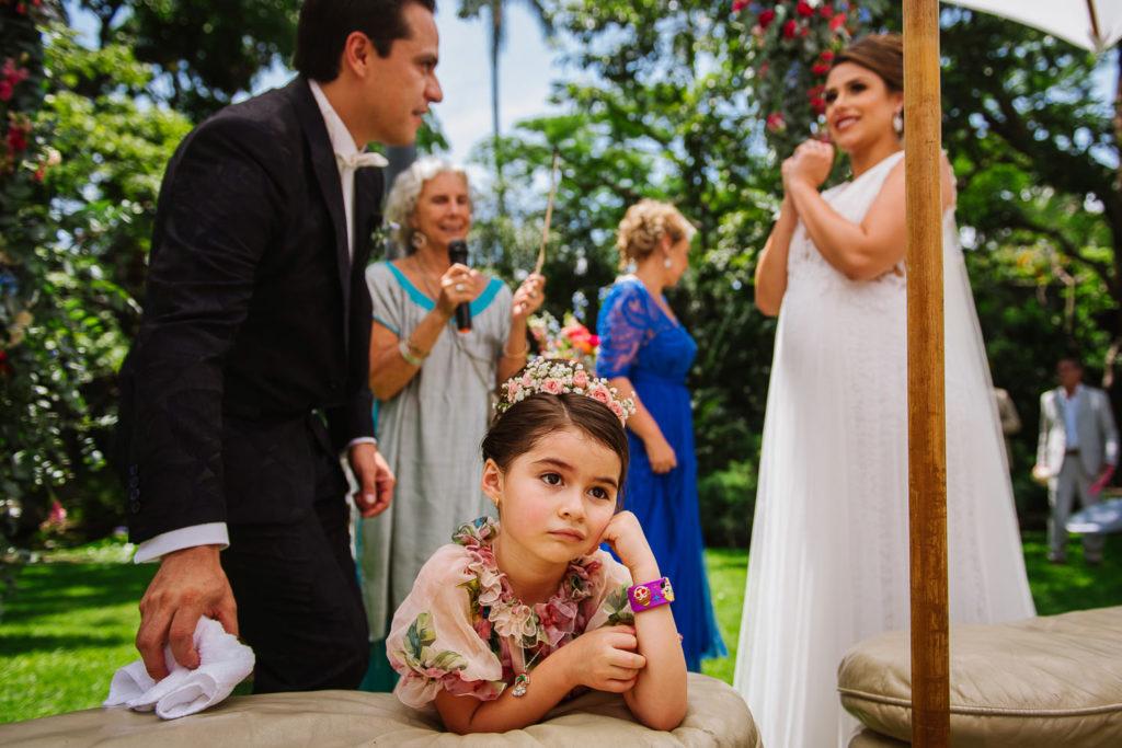 Flower girl bored during garden wedding ceremony