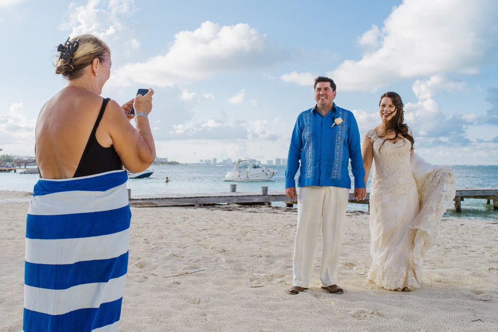 Random women with a striped towel taking a picture of a bride and groom on the beach in Cancun