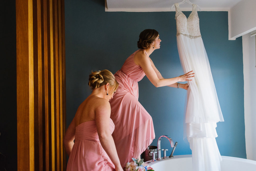 Bridesmaids with pink dresses hanging dress by the window at Azul Senatori Room