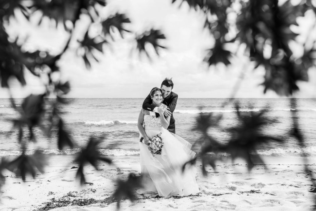 black and white portrait of groom holding bride from behind playing on the beach framed with tree branches and leaves at Blue Venado beach club