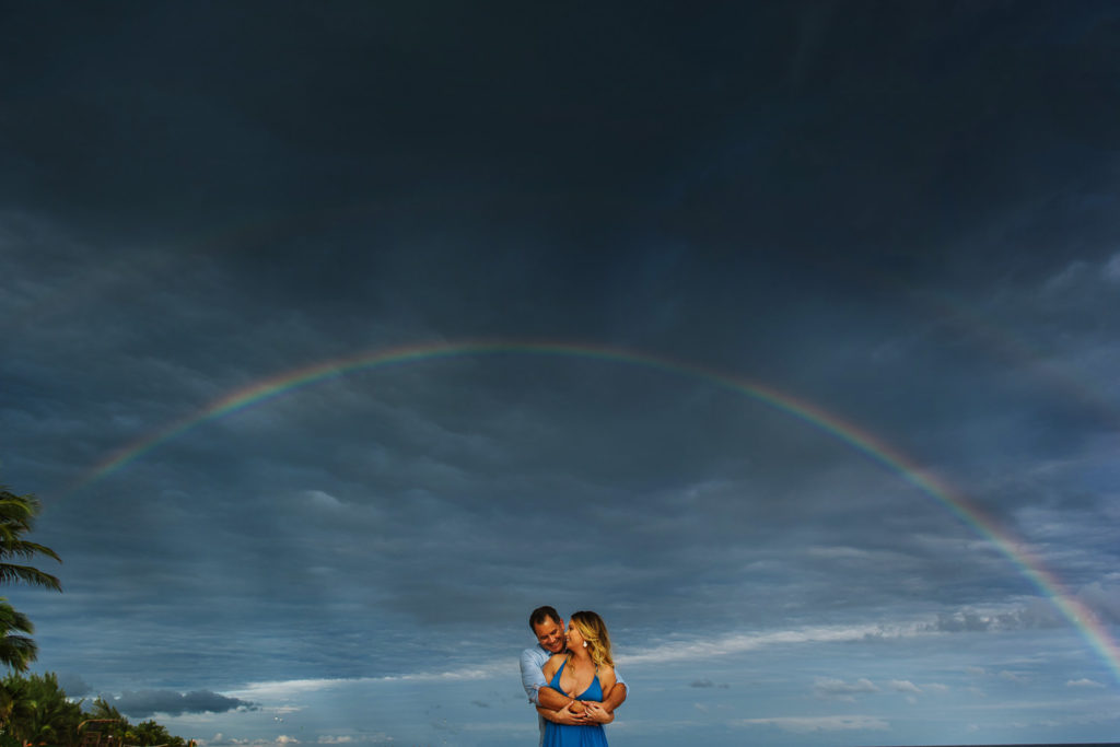 Double Rainbow on the sky with couple posing on Playa del Carmen beach at Hotel LeReve