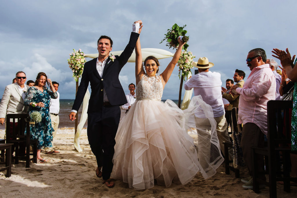 Bride and groom raise their holding hands in joy after ceremony on the beach in Riviera Maya