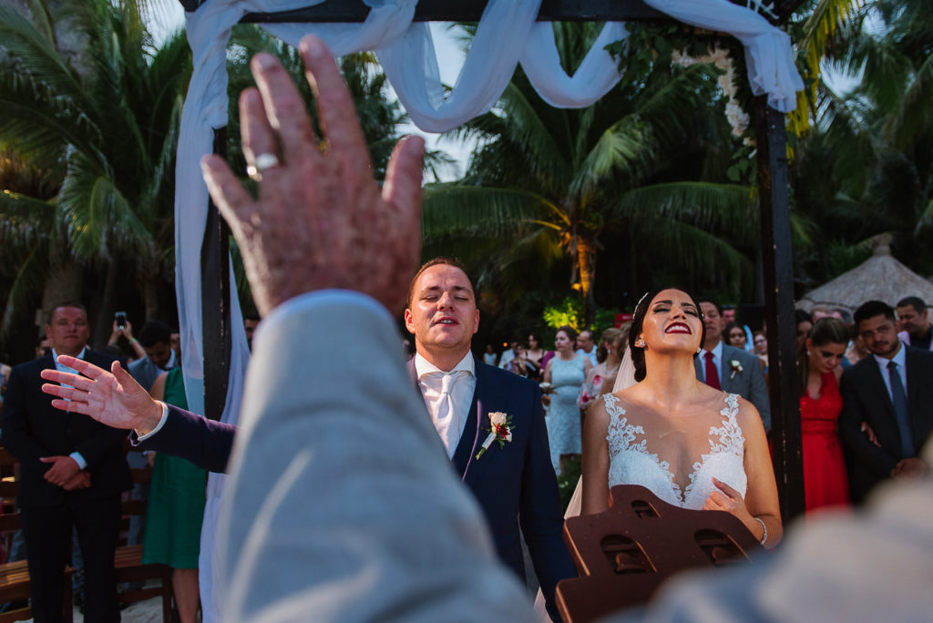 Christian ceremony image of bride and groom singing with minister's hand in the foreground in Xcaret Mexico