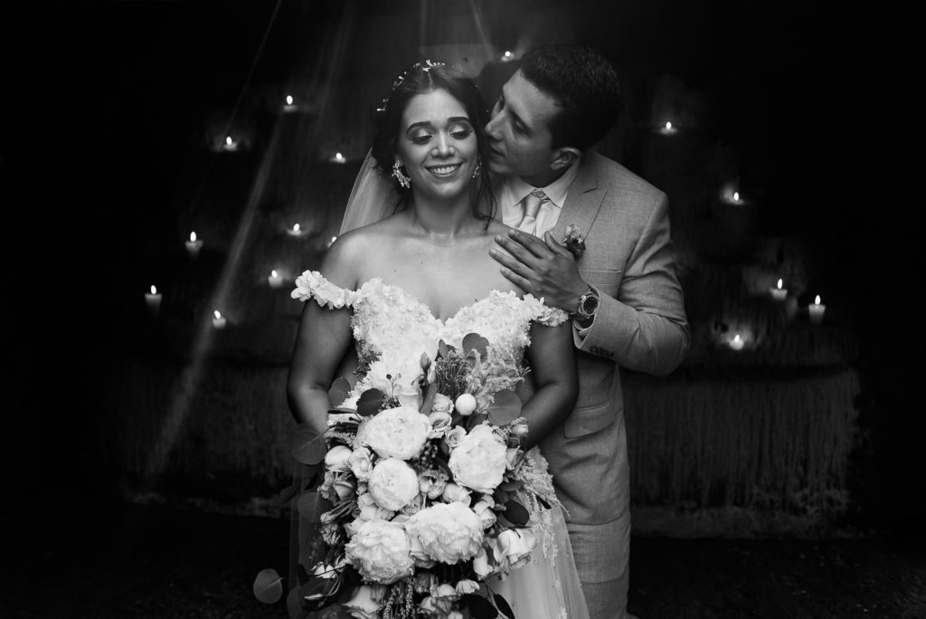 Xcaret wedding portrait in black and white of bride and groom lid with magical sunlight and candles in the back