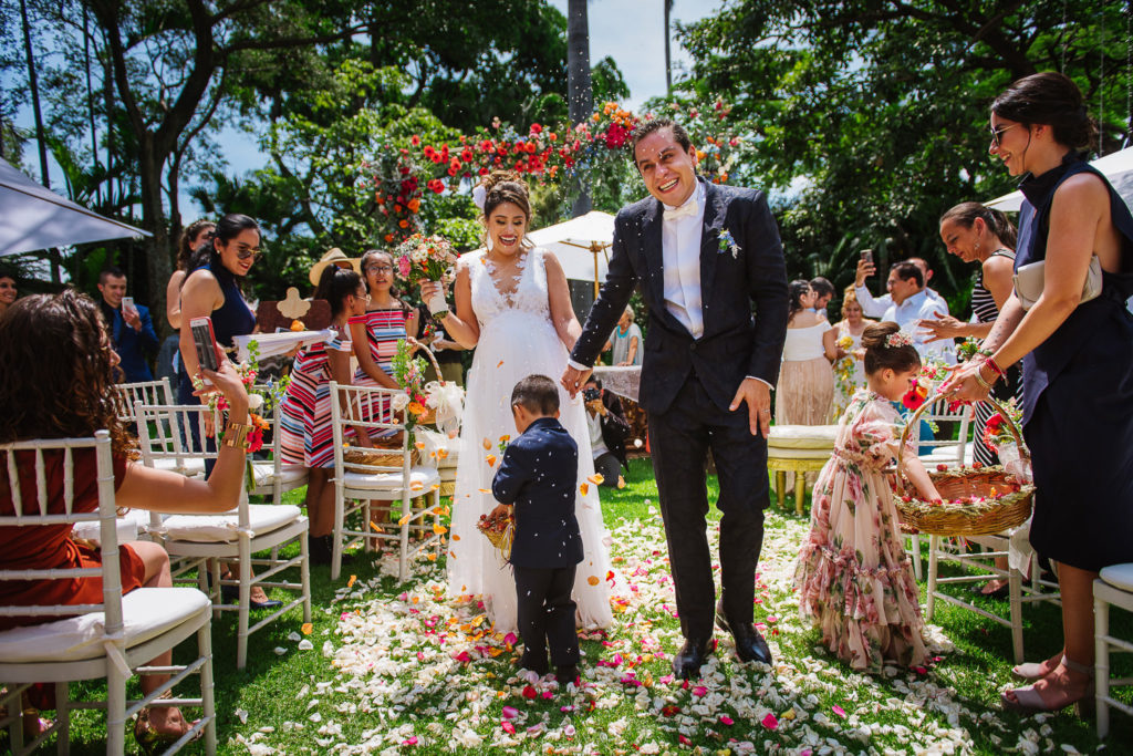 guests toss rice and flower pedals to bride and groom walking out the aisle in a garden wedding in Cuernavaca