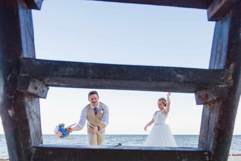 Bride and groom framed with a wooden ladder on the beach while groom catches the bouquet