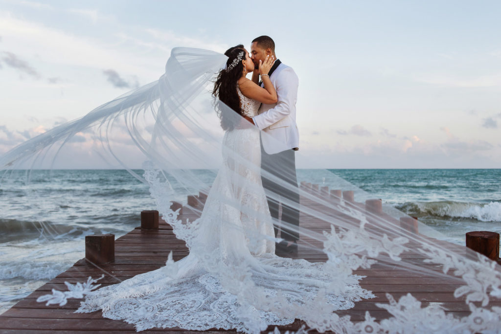 Bride and groom gorgeous portrait wraped around with a cathedral veil kissing on pier by the ocean