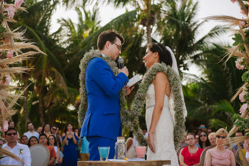 Groom reads his vows to bride during ceremony in Playa del Secreto