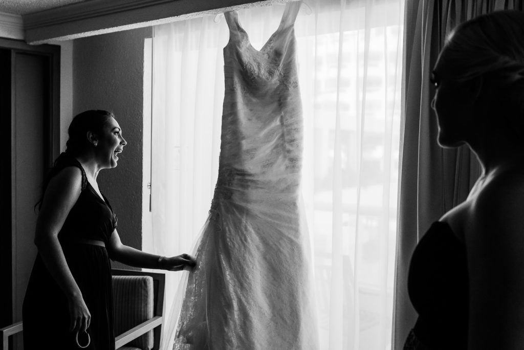 Bridesmaids checking out the dress hanging from the window in hotel room in Cancun